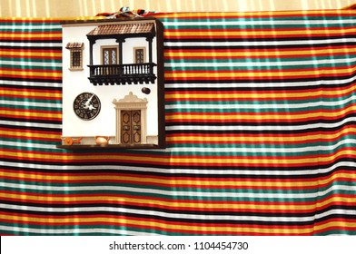 Colorful image with a facade of a traditional miniature house hanging on the wall with a cloth underneath