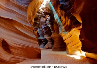 Colorful image of a sun light beam shining through the Upper Antelope slot Canyon.