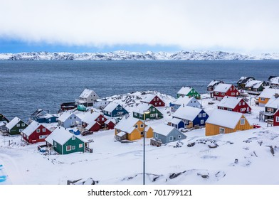 Colorful inuit houses among rocks and snow at the fjord in a suburb of arctic capital Nuuk, Greenland