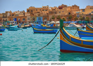 The colorful island of Malta. Blue-yellow fishing boats on the turquoise sea against orange ancient buildings. Fishing port, view from the water surface. Holidays in Malta.