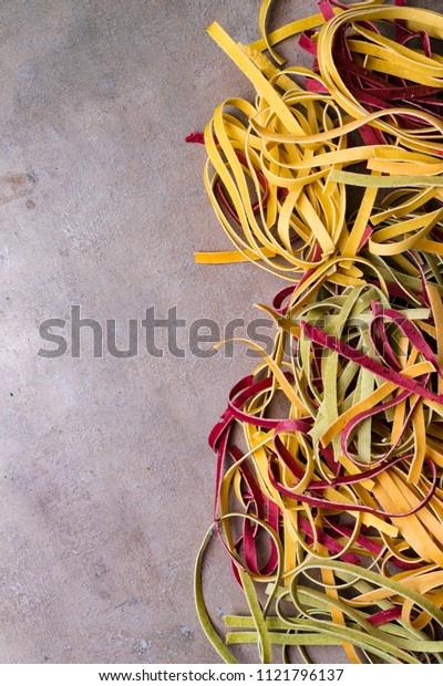 colorful italian pasta on grey background. Spaghetti wallpaper and space for your text.