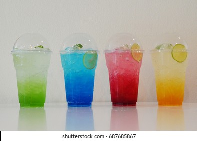 Colorful italian soda in plastic cup isolated on white background