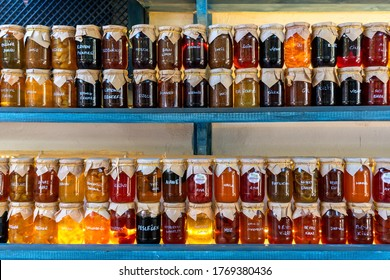 """Colorful jams in glass jars. Translation: """"different fruit names""""."""