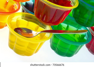Colorful jellies in plastic bowls arranged in a pile with a teaspoon (Selective Focus, Focus on the teaspoon)