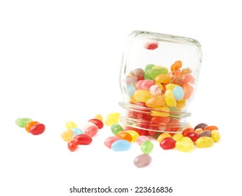 Colorful jelly bean candy sweets spilled out of a glass jar, composition isolated over the white background