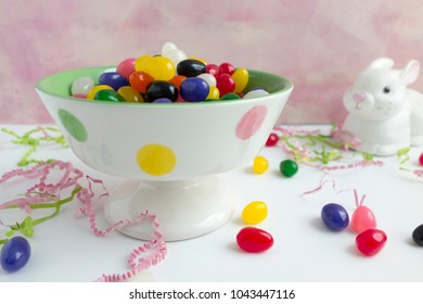 Colorful jelly beans in a polka dot bowl with scattered Easter grass and a rabbit figure in the background against a pink background.