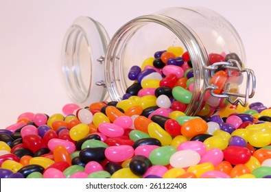 Colorful Jelly Beans Scattered from Spilled Glass Jar On