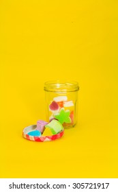Colorful jelly candies in jar on yellow background
