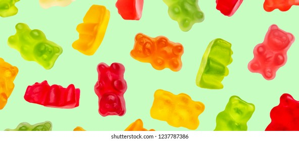 Colorful jelly candy gummy bears falling over green background. Red, green, orange and yellow colors.
