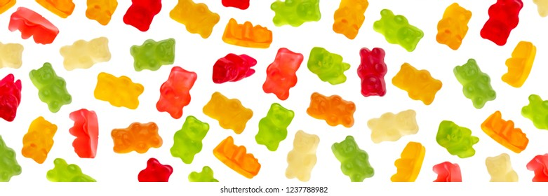 Colorful jelly candy gummy bears falling over white background. Red, green, orange and yellow gummy bear colors. Panorama view