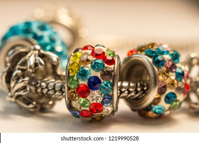 Colorful jewelry, with multicolored inlaid stones, strung with silver bracelet, macro