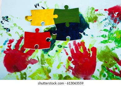 Colorful jigsaw puzzle with hand prints as a background. Conceptual for Autism Awareness Month