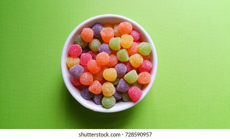Colorful jujubes on green background top view