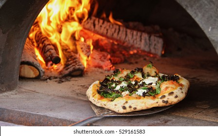 Colorful kale pizza being pulled from mobile wood fired oven food truck at a catering event