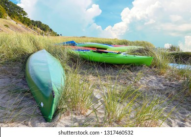 colorful kayaks in dune grass on Lake Michigan beach