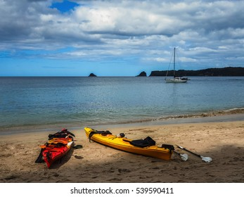 Colorful Kayaks on the beach and a Yacht floating on the sea in New Zealand
