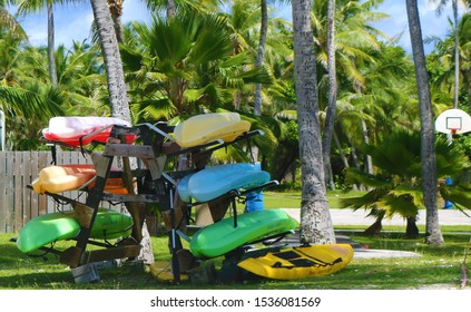 Colorful Kayaks on rack with tropical background
