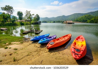 Colorful kayaks parked by lake, dam in Thailand. The kayaks have different colors, blue, purple, orange, red, and yellow for attracting adventurists to rent and enjoy kayaking under the sun in summer.
