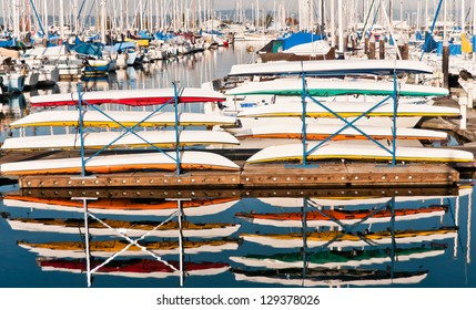 Colorful kayaks stacked on a pier in a marina and reflection of boats in water