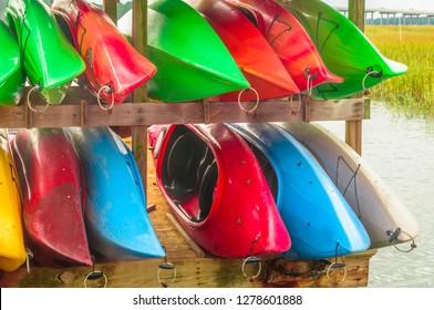 Colorful kayaks tied up on Hilton Head Island dock on water.
