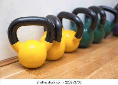 Colorful kettle bells on the floor in the gym