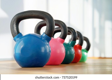 Colorful kettlebells in a row in a gym