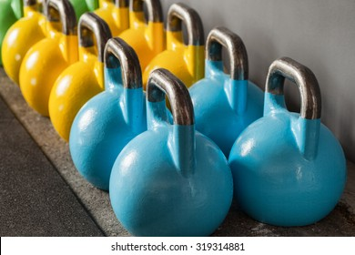 colorful kettlebells in a row in a gym - focus on the front kettle bell