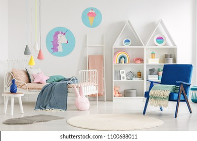 Colorful kid's bedroom interior with a unicorn and ice-cream poster, bed with sheets, rabbit pillow, shelves and blue armchair with a blanket