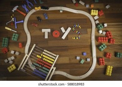Colorful kids toys background frame with many toys on wooden floor background. Flat lay. Top view.