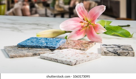 Colorful kitchen counter samples on white carrara marble surface and lily flower