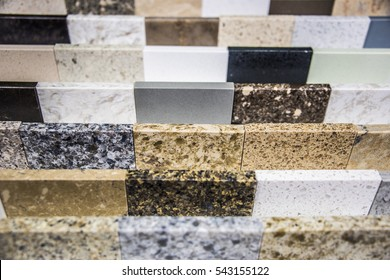 Colorful kitchen counter top samples made of granite marble and quartz natural stone slabs lined up in store