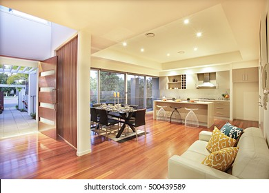 Colorful kitchen with facilities and wooden floor, expensive furniture can see in this room, door and shiny floor made with wood, pillows with designs on the sofa, trees with flowers in the garden.