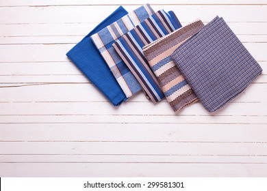 Colorful kitchen towels  on white painted wooden background. Selective focus. Place for text.