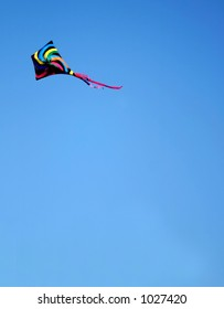 A colorful kite in a bright blue sky.