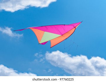 Colorful Kite - flying against blue sky and clouds