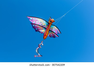 A colorful kite flying in the wind on a clear sunny day.