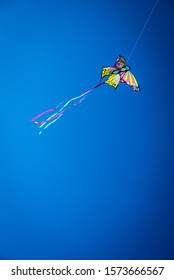 Colorful kite with long tail flying in the blue sky against the sun, copy space.