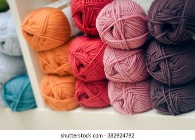 Colorful knitting yarn on shelf, closeup photo
