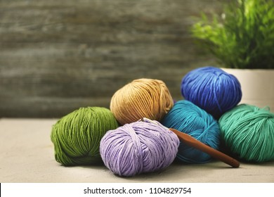 Colorful knitting yarns and crochet on table indoors