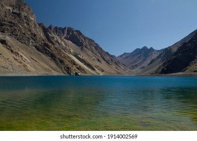 The colorful lake called Inca Lagoon in the Andes mountain range. The blue glacier water and yellow shallows surrounded by rocky mountains.