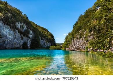 Colorful lake framed by steep rocks - Plitvice lakes in Plitvice National Park, Croatia