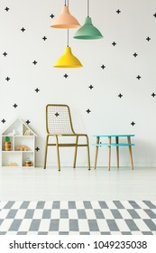 Colorful lamps above gold chair and blue table in girl's playroom interior with wallpaper