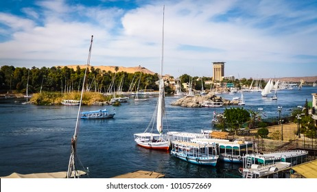 Colorful landscape with boats on a busy river. Nile river in Aswan with tourist boats, feluccas and yachts