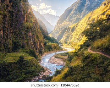 Colorful landscape with high Himalayan mountains, beautiful curving river, green forest, blue sky with clouds and yellow sunlight at sunset in summer in Nepal. Mountain valley. Travel in Himalayas - Shutterstock ID 1104475526