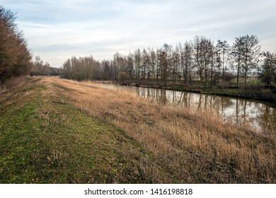 Colorful landscape with the narrow river Donge and an embankment in a Dutch nature reserve near the village of Raamsdonksveer,  North Brabant. The photo was taken in the winter season.