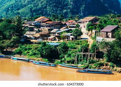 Colorful landscape of Nong Khiaw and orange-yellow muddy Ou river with local boats, Laos