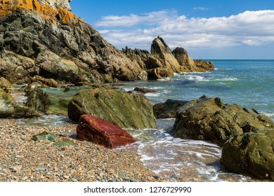 Colorful landscape with rugged cliffs at the Irish Sea shore and a small pebble beach on a beautiful sunny day in Howth, Dublin, Ireland.