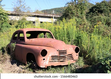 "A colorful landscape with a rusty abandoned body of the legendary Soviet car ""Victory"" in Abkhazia. Atmospheric, juicy textured picture with abandoned equipment."