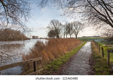 Colorful landscape with a small river, reeds and a country road with some snow.