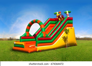 Colorful, large, inflatable children's slide on the green grass